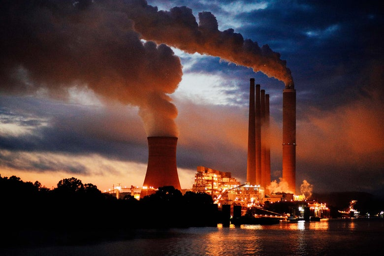 Coal-fired power plant lights up the early morning sky on the banks of the river.